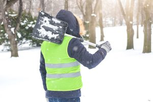 Rear view of man holding shovel over his shoulder and preparing for shoveling snow.